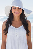 Happy brunette in white sunhat smiling at camera