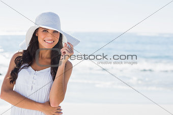 Beautiful brunette in white sunhat smiling at camera