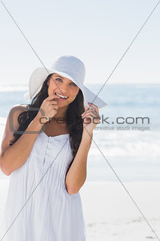 Beautiful brunette in white sunhat looking at camera