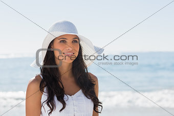 Beautiful brunette in white sunhat looking away