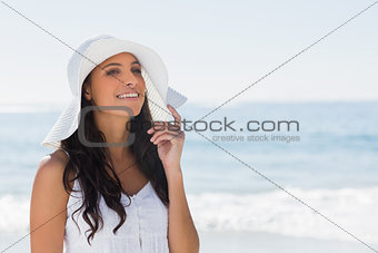 Beautiful brunette in white sunhat looking away and touching hat