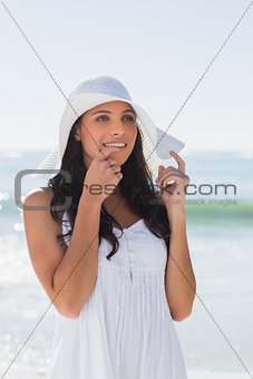 Pretty brunette in white sunhat looking away and touching hat