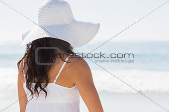 Pretty brunette in white sunhat looking at the ocean