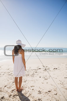 Brunette in white sunhat and dress looking at the ocean