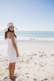 Brunette in white sunhat and dress looking over her shoulder at camera