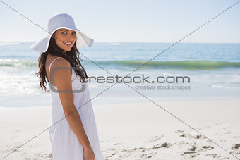 Brunette in white sunhat looking over her shoulder at camera