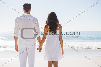 Attractive couple holding hands and watching the ocean