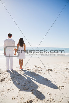 Attractive couple holding hands and watching the sea