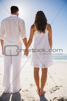 Attractive couple holding hands and watching the water