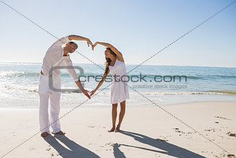 Cute couple forming heart shape with arms