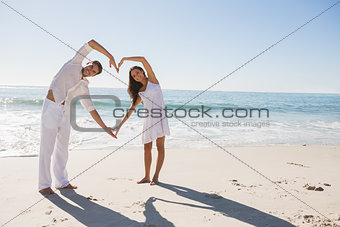 Loving couple forming heart shape with arms