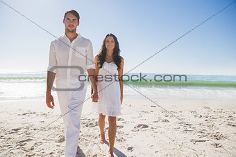 Beautiful couple holding hands and walking towards camera