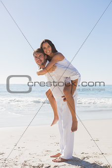 Handsome man giving happy girlfriend a piggy back