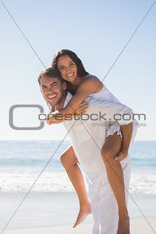 Smiling man giving happy girlfriend a piggy back