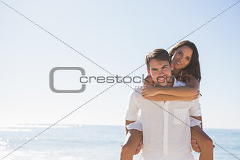 Smiling man giving girlfriend a piggy back looking at camera