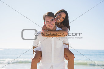 Handsome man giving girlfriend a piggy back smiling at camera