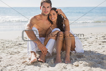 Cuddling couple smiling at camera