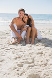 Cuddling couple smiling at camera sitting on sand