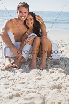Embracing couple smiling at camera sitting on sand