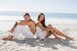 Couple sitting back to back on the sand smiling at camera