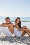 Couple sitting back to back on sand smiling at camera