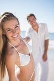 Blonde woman smiling at camera with boyfriend holding her hand