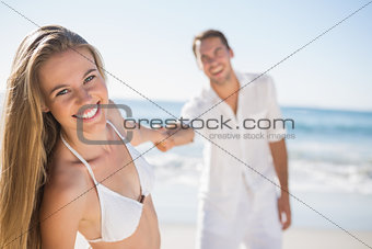 Pretty woman smiling at camera with boyfriend holding her hand