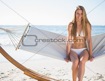 Pretty blonde sitting on hammock and smiling
