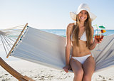 Pretty blonde wearing bikini and sunhat sitting on hammock with cocktail