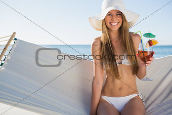 Happy blonde wearing bikini and sunhat sitting on hammock with cocktail