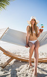 Cheerful blonde wearing bikini and sunhat sitting on hammock with cocktail