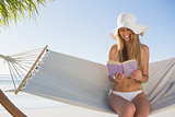 Smiling blonde wearing sunhat sitting on hammock reading book
