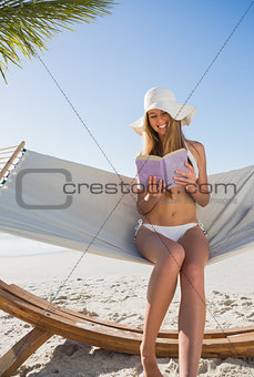 Happy blonde wearing sunhat sitting on hammock reading book