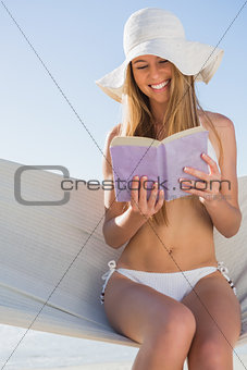 Happy blonde sitting on hammock reading book