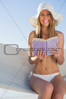 Happy blonde sitting on hammock holding book