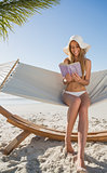 Cheerful blonde sitting on hammock reading book