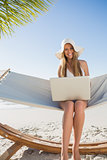Smiling blonde sitting on hammock using laptop
