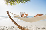 Woman wearing sunhat and bikini relaxing on hammock