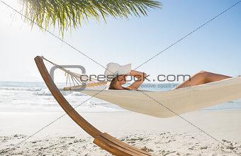 Woman wearing sunhat and bikini relaxing on hammock