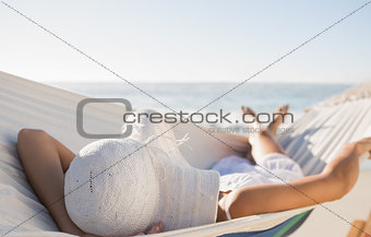 Peaceful woman in sunhat relaxing on hammock