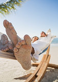 Close up of sandy feet of couple sleeping in a hammock