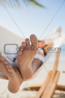 Close up of sandy feet of woman sleeping in a hammock