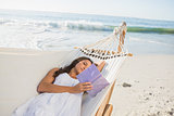 Woman lying on hammock reading book