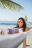 Woman lying on hammock holding book and smiling at camera