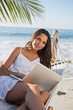 Brunette sitting on hammock with laptop smiling at camera