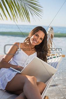 Brunette sitting on hammock using laptop smiling at camera