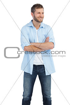 Smiling man crossing arms and looking away