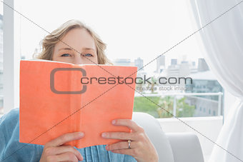 Blonde woman sitting on her couch covering face with orange book