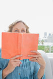 Woman sitting on her couch covering face with orange book
