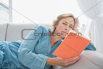 Content blonde woman relaxing on her couch reading book